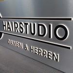 Aussenwerbung Projekt DC Hairstudio in Sarstedt von Dirim-Media Webdesign- & Werbeagentur in Hannover. Leuchtkasten mit gefrästen durchgesteckten Buchstaben als Seitenansicht beleuchtet. Hintergrund gebürstete Metall-Optik.
